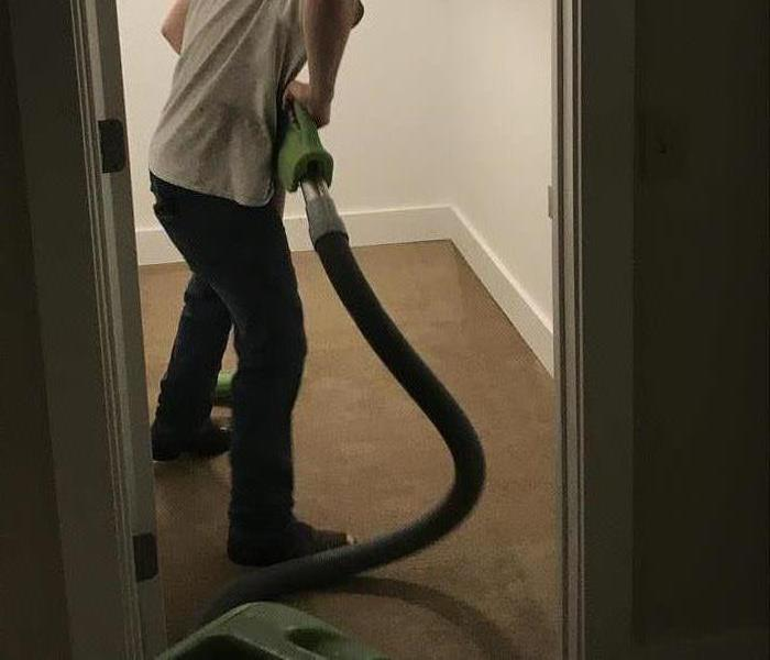 Guy removing water from carpet with a extraction wand