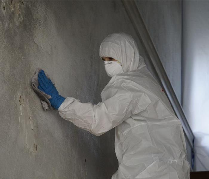A man using a rag to remove soot damage